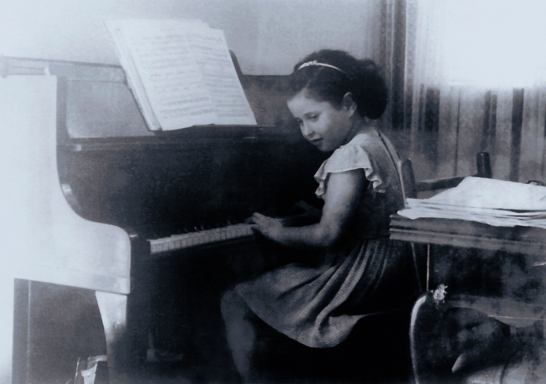 Tsippi as a child beside the piano